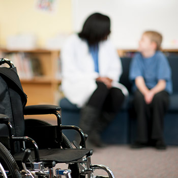 Child and woman talking behind a wheelchair.