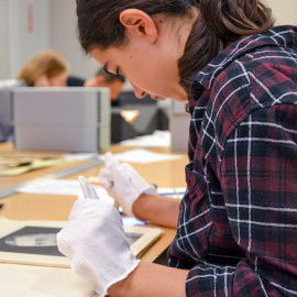 Image of student working with archival material