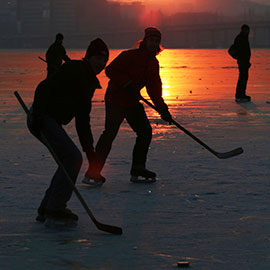 people playing hockey on outdoor rink