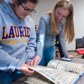 Students looking at reproduction of medieval manuscript
