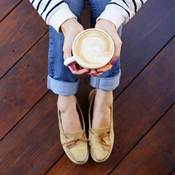 Image of a person sitting on the ground holding cup of coffee