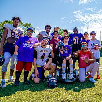 Laurier football players and Light House members pose for a group photo.