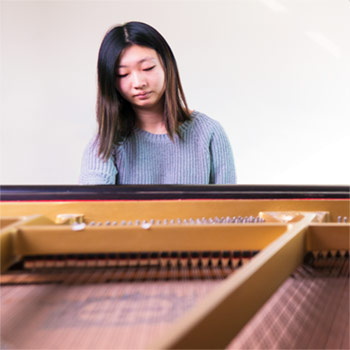Image of Janet Lu, music student, seated at a piano.