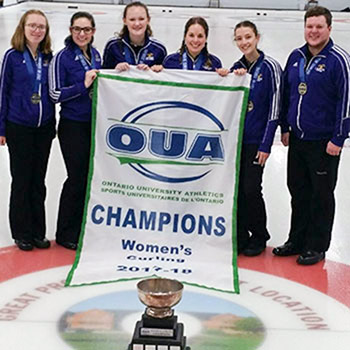 women's curling team with banner and trophy