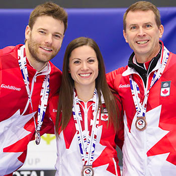 curling players posing with medals